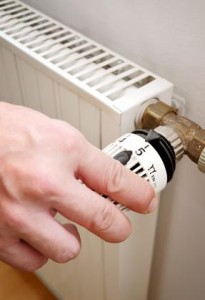 Main règlant un robinet thermostatique